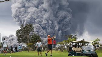 HAWAII VOLCANOES NATIONAL PARK, HI - MAY 15:  People play golf as an ash plume rises in the distance from the Kilauea volcano on Hawaii's Big Island on May 15, 2018 in Hawaii Volcanoes National Park, Hawaii. The U.S. Geological Survey said a recent lowering of the lava lake at the volcano's Halemaumau crater 'has raised the potential for explosive eruptions' at the volcano.  (Photo by Mario Tama/Getty Images)