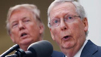 U.S. President Donald Trump listens as Senate Majority Leader Mitch McConnell speaks to the media in the Rose Garden of the White House in Washington, U.S., October 16, 2017. REUTERS/Kevin Lamarque