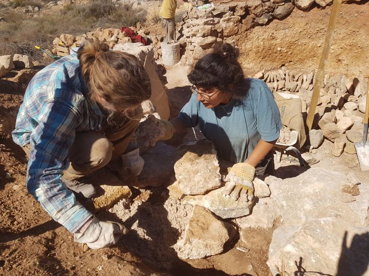 Two volunteers, Fran and Amneh, build a stone roundhouse to house visitors.