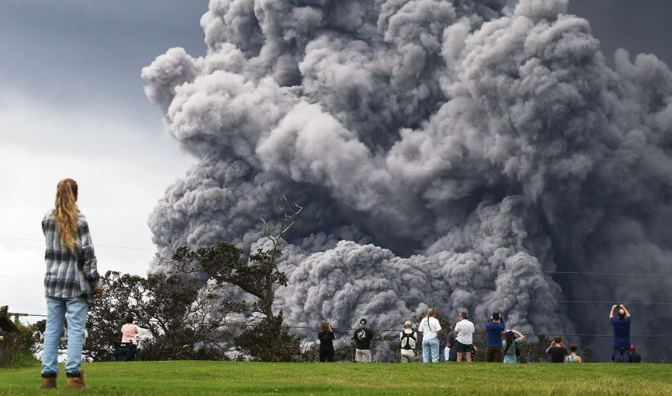 People watch at a golf course as an ash plume rises in the distance from the Kilauea volcano on Hawaii's Big Island in Hawaii