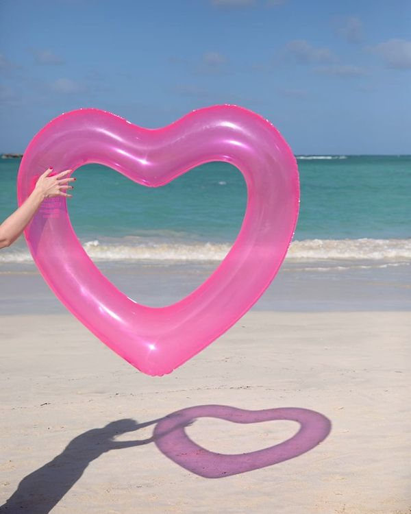 """Get it on <a href=""""https://www.bando.com/collections/pool-floats/products/beach-please-heart-innertube-translucent-neon-pink"""""""