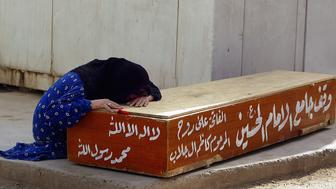 BAGHDAD, IRAQ - MARCH 30:  An Iraqi woman weeps over a coffin cry at a hospital in the Sadr city district following the death of a relative who was killed during last nights clashes between Mahdi army militiamen and Iraqi/U.S forces on March 30, 2008 in Baghdad, Iraq. Sadr militia have now been ordered to withdraw from the streets of all neighbourhoods by Iraqi Shia cleric Moqtada Sadr, who stated that he wanted a stop to the bloodshed and to maintain Iraq's independence and stability. (Photo by Wathiq Khuzaie/Getty Images)