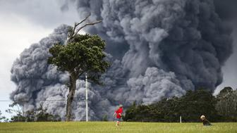 HAWAII VOLCANOES NATIONAL PARK, HI - MAY 15: Kids play at a golf course as an ash plume rises in the distance from the Kilauea volcano on Hawaii's Big Island on May 15, 2018 in Hawaii Volcanoes National Park, Hawaii. The U.S. Geological Survey said a recent lowering of the lava lake at the volcano's Halemaumau crater 'has raised the potential for explosive eruptions' at the volcano.  (Photo by Mario Tama/Getty Images)