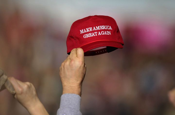 "A supporter holds up a ""Make America Great Again"" hat during the April 28 rally."
