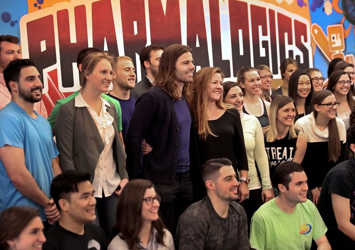 PharmaLogics employees pose with their CEO Megan Driscoll (center right) and Dan Price (center left), who influenced Meg