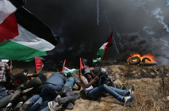 Palestinian demonstrators take cover from Israeli fire and tear gas during a protest against U.S. embassy move to Jerusalem.
