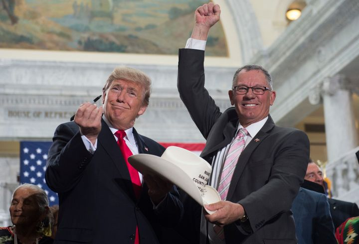 President Donald Trump holds up a pen after signing the hat of Bruce Adams, chairman of the San Juan County Commission, after