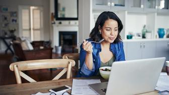 Shot of a young woman using a laptop and having a salad while working from home