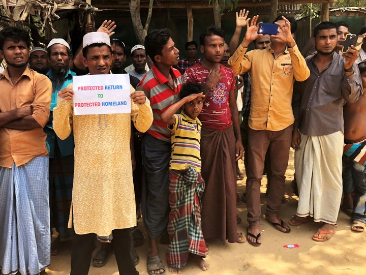 Rohingya refugees line the streets as United Nations Security Councilvehicles passoutside Kutupalong Refugee Camp
