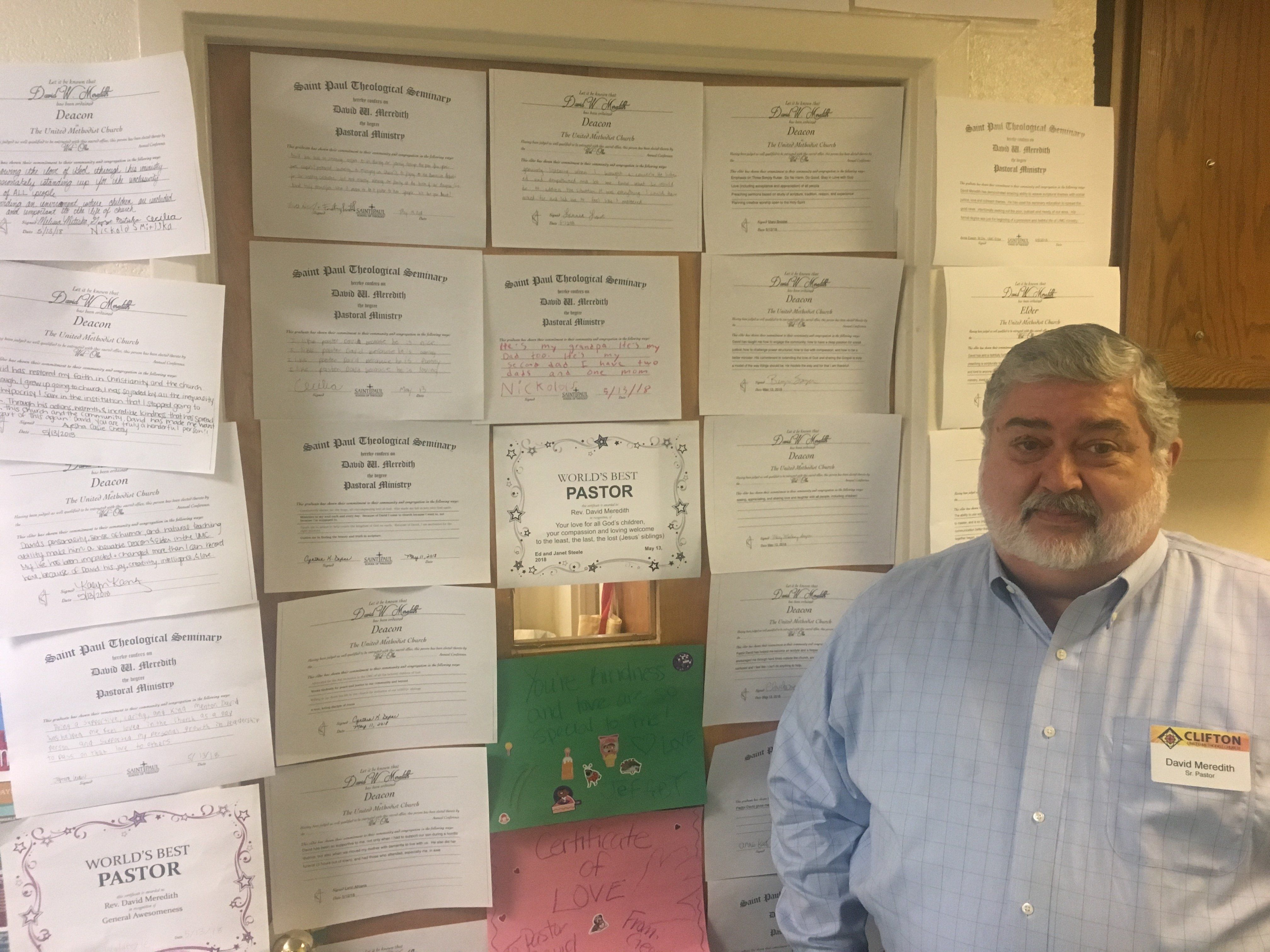 The Rev. David Meredith stands next toa door with supportive messages from his congregation at Clifton United Methodist
