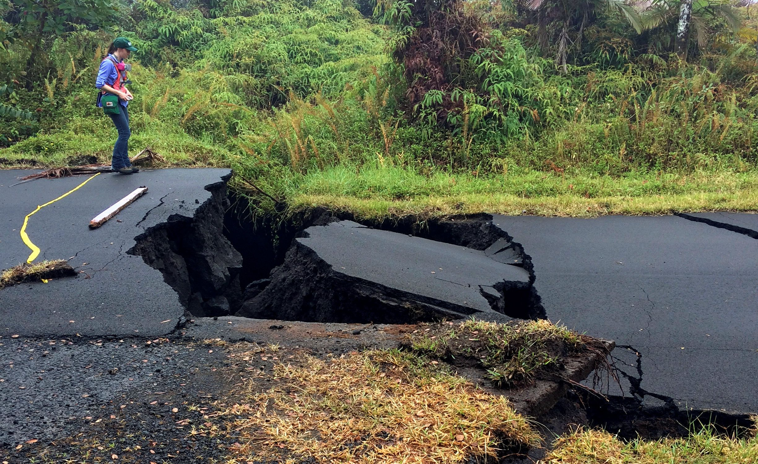A geologist inspects cracks on a road in Leilani Estates, following eruption of Kilauea volcano, Hawaii...