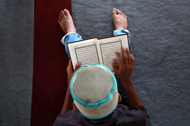 Un garçon lit le coran avant le début de la prière du vendredi pendant le mois de ramadan dans une mosquée...