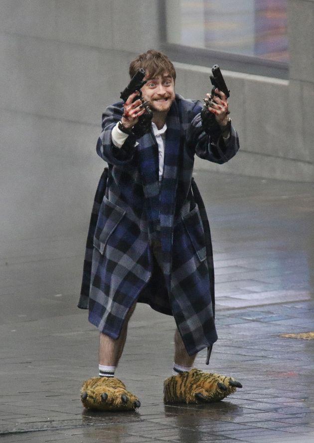 Daniel Radcliffe looking menacing while shooting guns and wearing tiger feet onset of