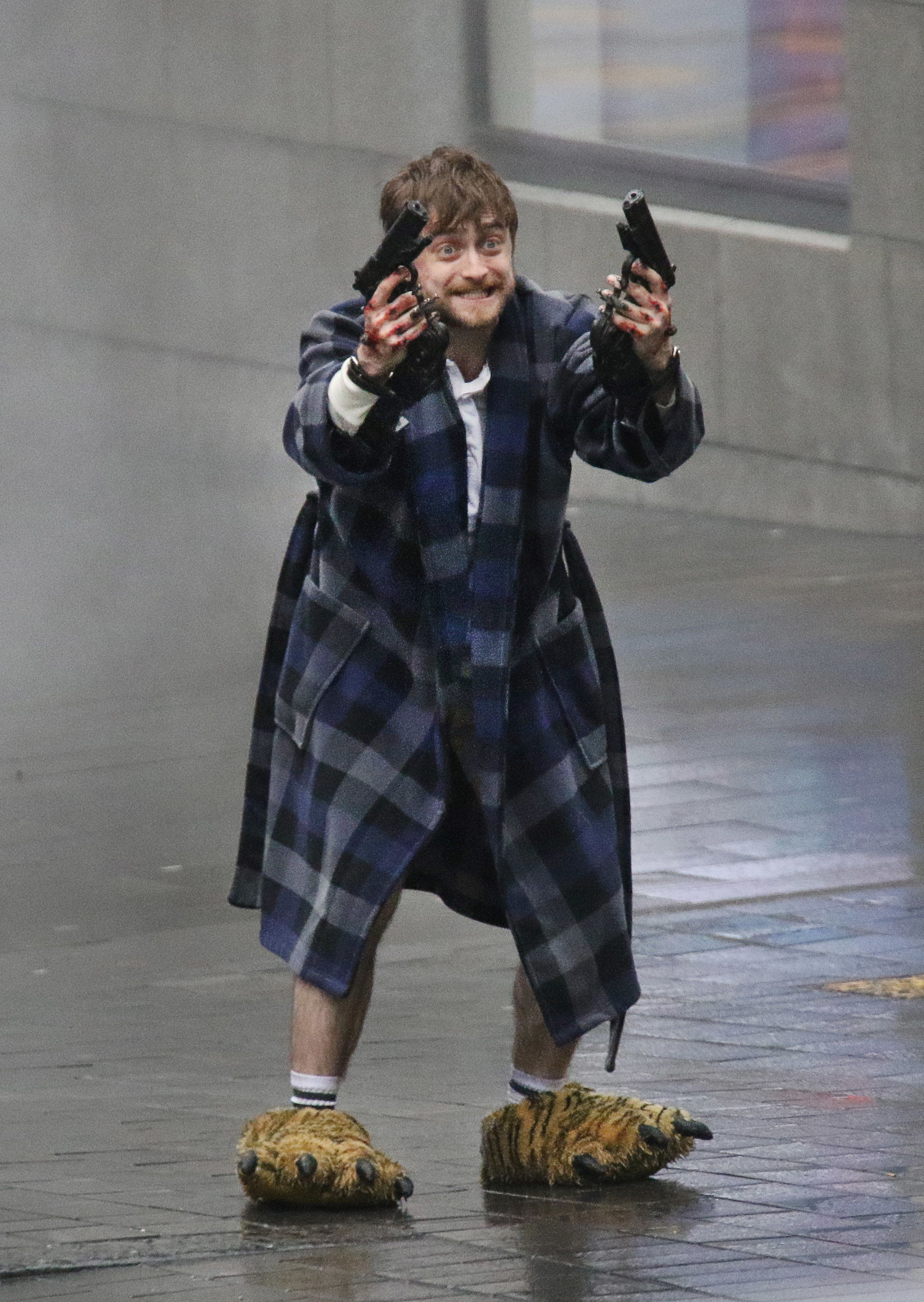 "Daniel Radcliffe looking menacing while shooting guns and wearing tiger feet onset of ""Guns Akimbo"" in Auckland, New Zealand"