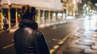 Young woman walking on the streets of London alone, wearing a black leather jacket and a backpack.