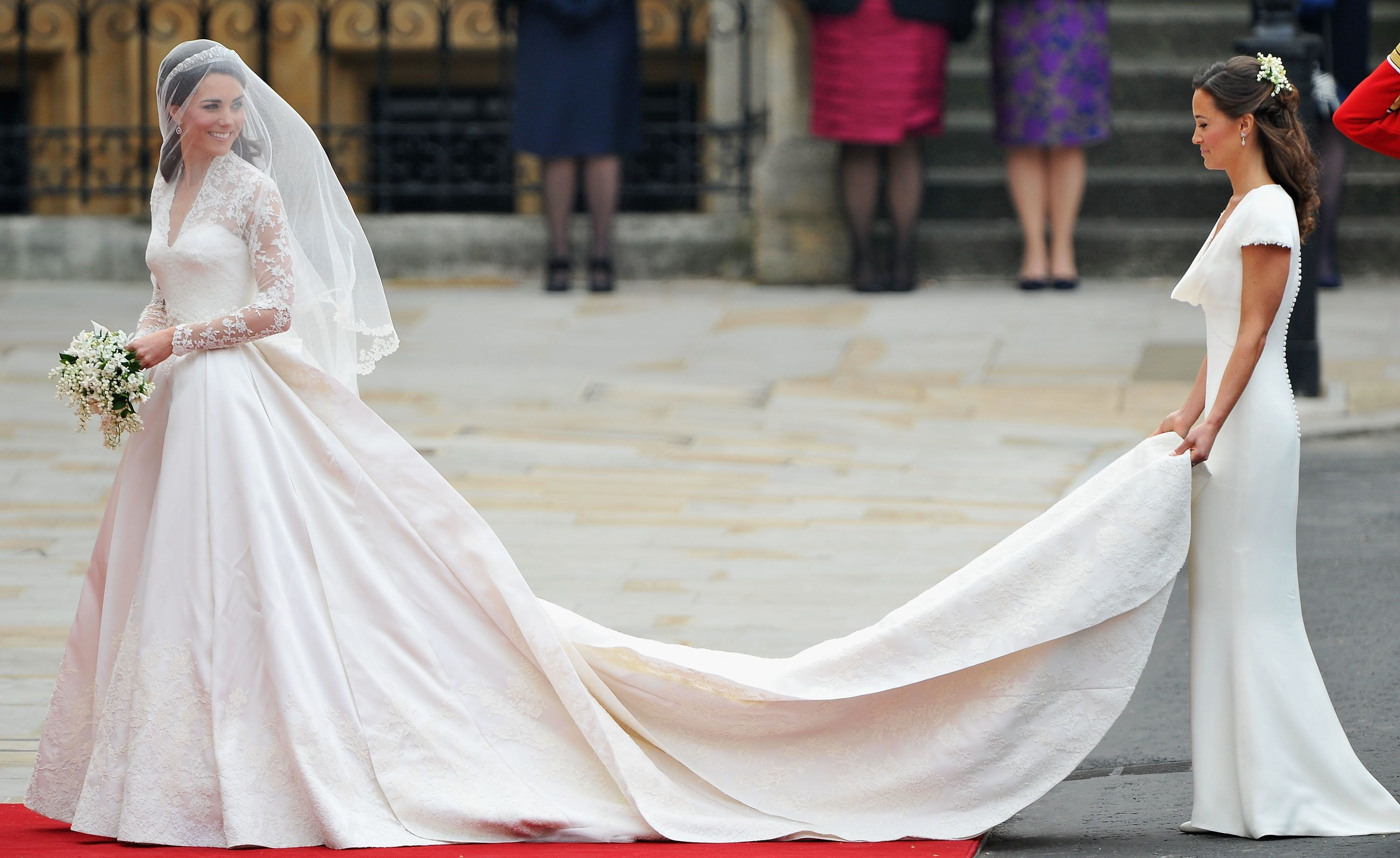 LONDON, ENGLAND - APRIL 29:  Catherine Middleton waves to the crowds as her sister and Maid of Honour Pippa Middleton holds her dress before walking in to the Abbey to attend the Royal Wedding of Prince William to Catherine Middleton at Westminster Abbey on April 29, 2011 in London, England. The marriage of the second in line to the British throne is to be led by the Archbishop of Canterbury and will be attended by 1900 guests, including foreign Royal family members and heads of state. Thousands of well-wishers from around the world have also flocked to London to witness the spectacle and pageantry of the Royal Wedding.  (Photo by Pascal Le Segretain/Getty Images)