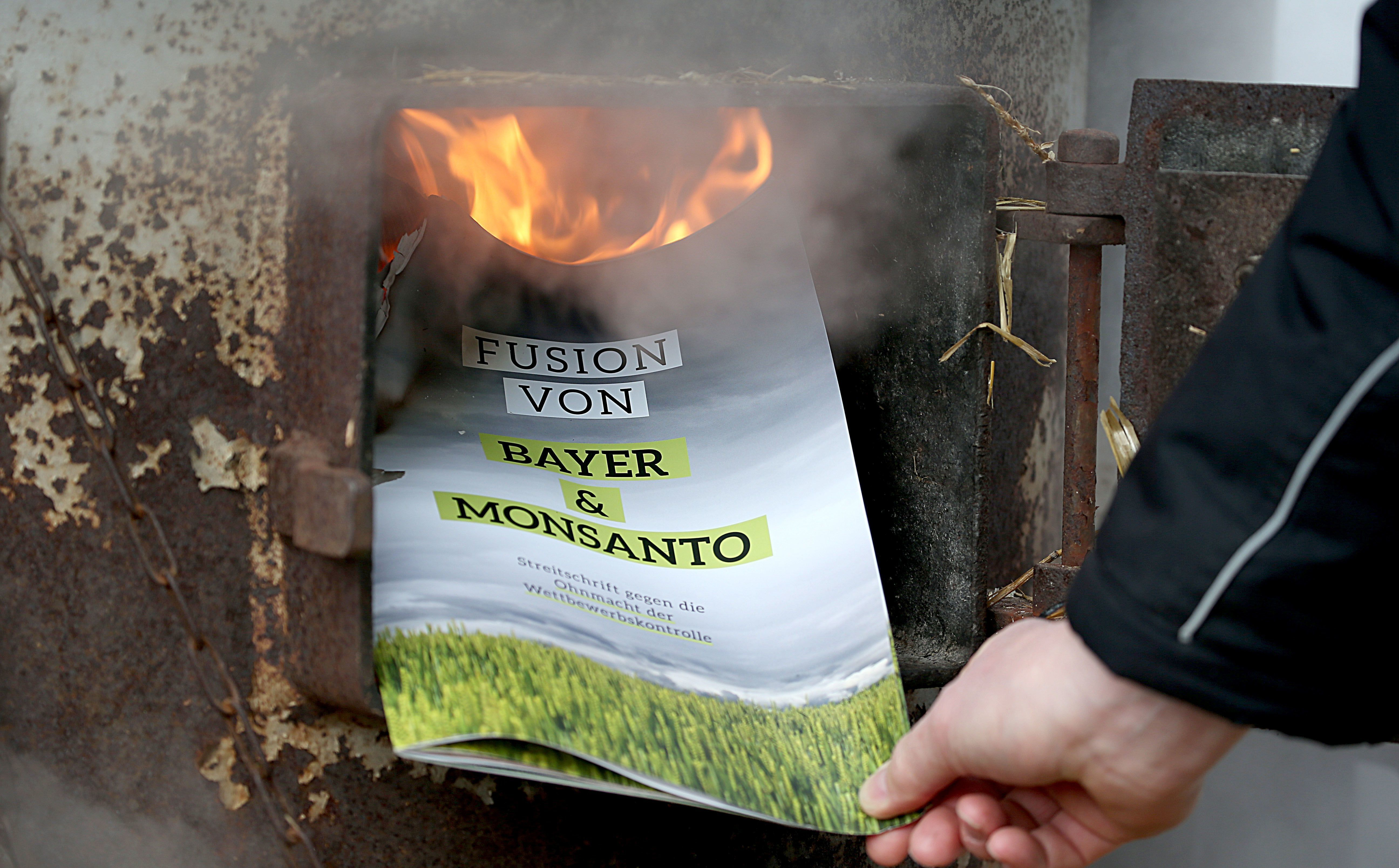 A protestor burns a leaflet during a demonstration in Bonn, Germany, against the merger between seed company Monsanto and pha