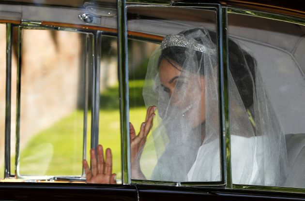 Meghan waves from the car on her way to the