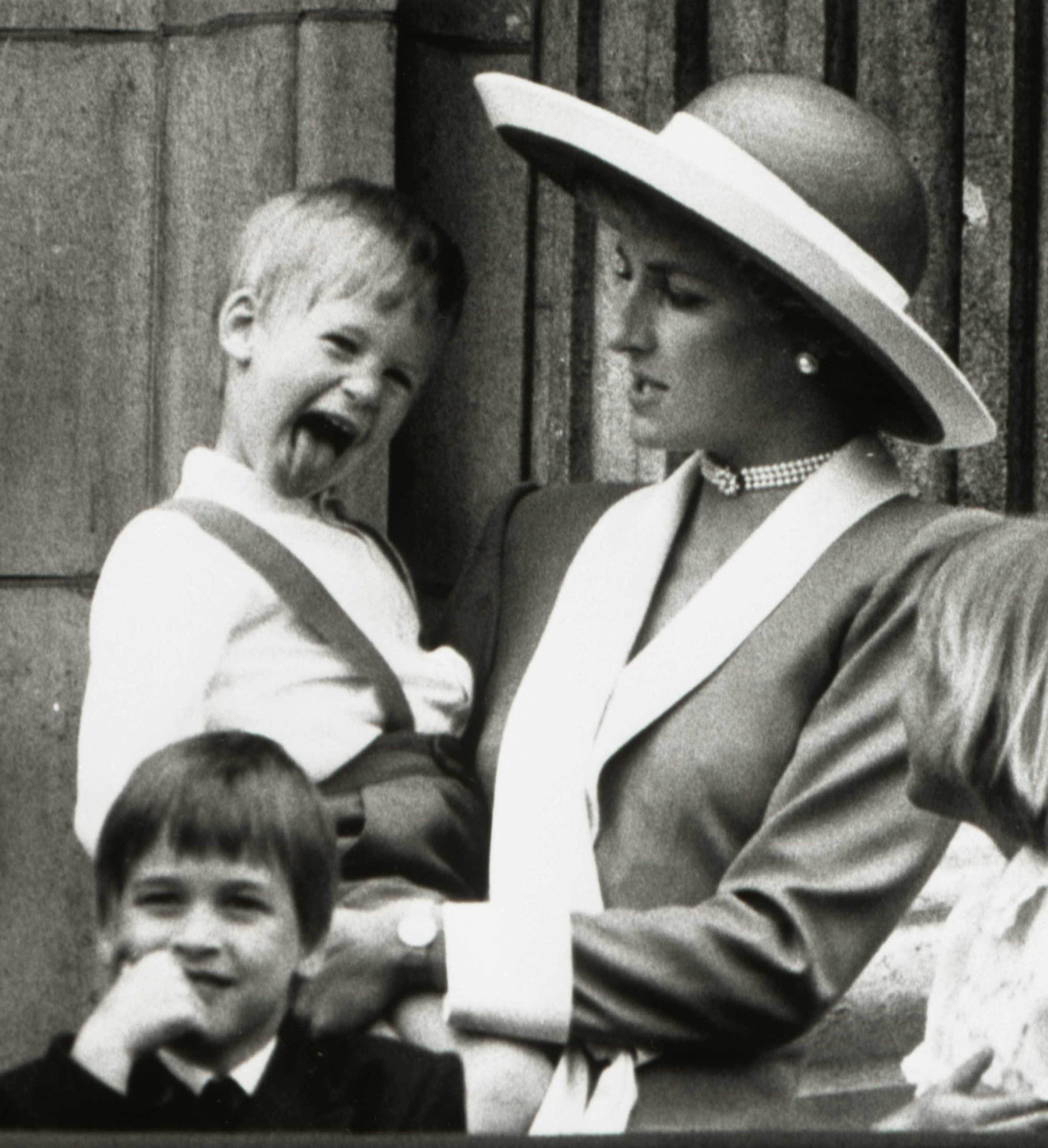 Princess Diana holds Prince Harry as her older son Prince William (L) looks out over the balcony of Buckingham Palace in London on June 11, 1988 after attending the Trooping the Colour ceremony, the Queen's birthday parade.  REUTERS/Stringer