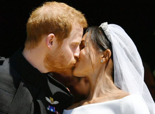 Prince Harry and Meghan Markle share a kiss.