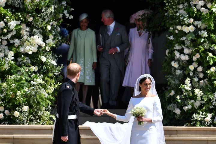 Harry turns around to find his father Charles taking good care of Meghan's mom.