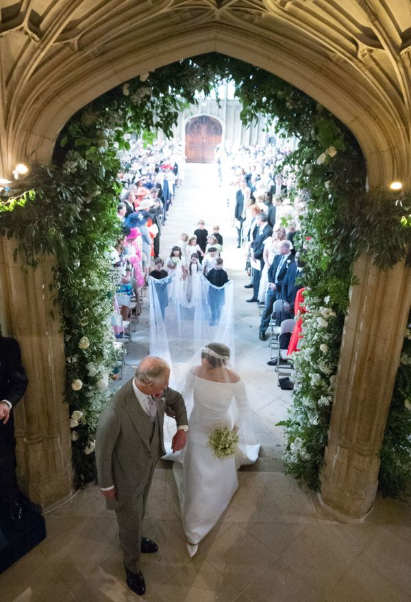 Meghan Markle walks up the aisle with Prince Charles, Prince of Wales at St George's Chapel at Windsor Castle.