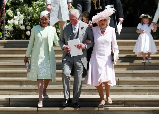 Charles walks arm-in-arm down the steps outside the chapel with both Ragland (left) and Camilla