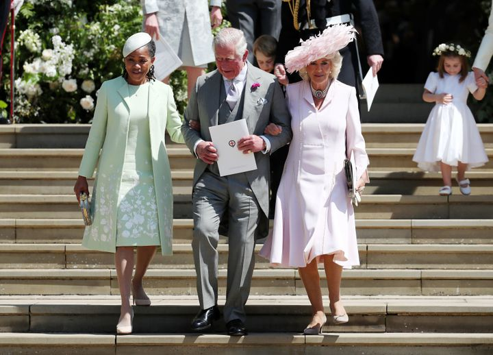 Charles walks arm-in-arm down the steps outside the chapel with both Ragland (left) and Camilla (right).