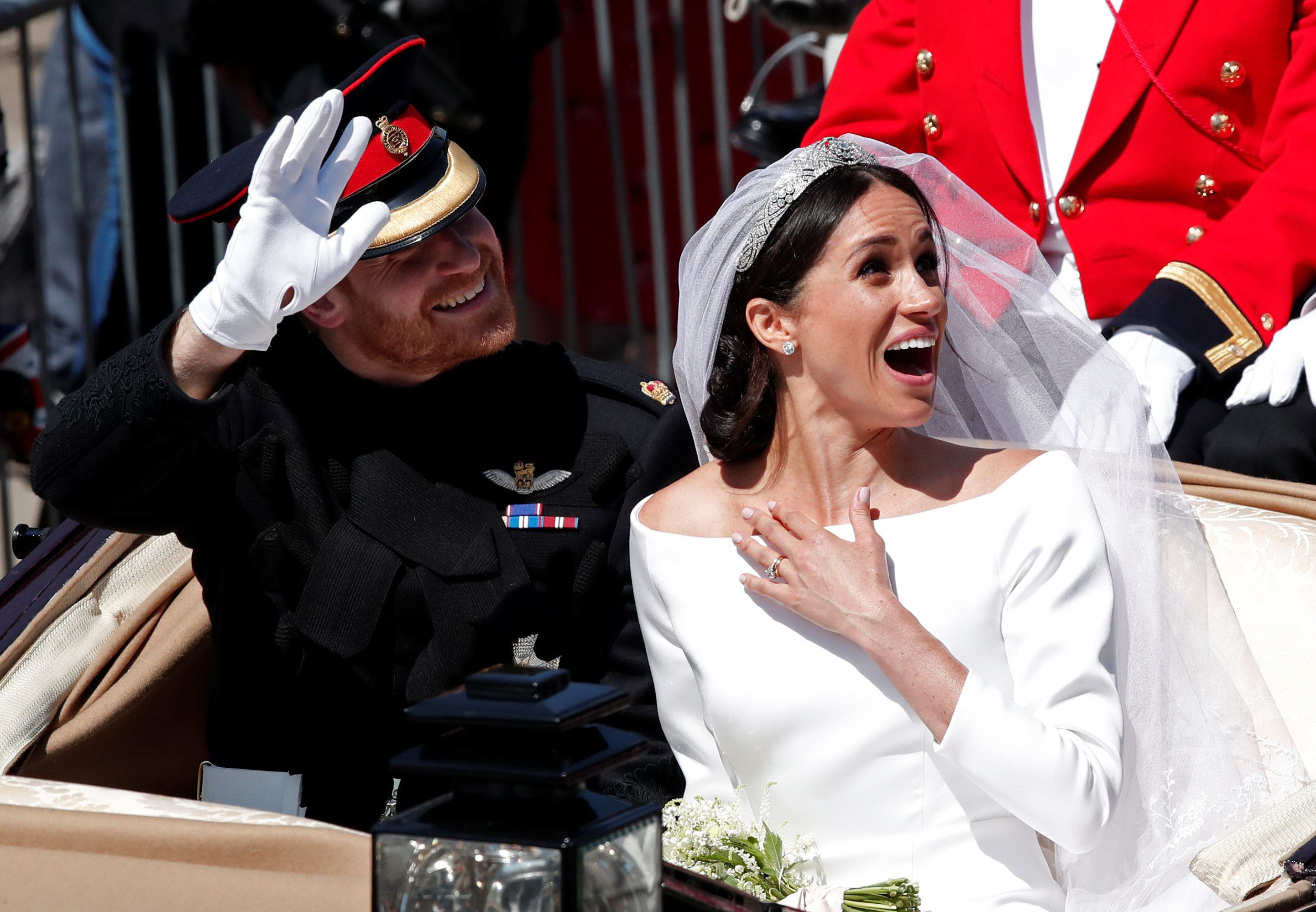 Britain?s Prince Harry and his wife Meghan ride a horse-drawn carriage after their wedding ceremony at St George?s Chapel in Windsor Castle in Windsor, Britain, May 19, 2018. REUTERS/Benoit Tessier TPX IMAGES OF THE DAY