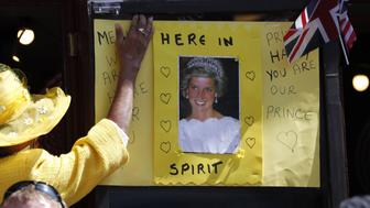 A Royal fan puts up a poster of Princess Diana, on Castle Hill during the wedding of Britain's Prince Harry, Duke of Sussex and Meghan Markle in Windsor, on May 19, 2018. (Photo by Frank Augstein / POOL / AFP)        (Photo credit should read FRANK AUGSTEIN/AFP/Getty Images)