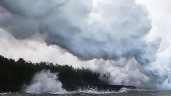 PAHOA, HI - MAY 20:  A steam plume rises from lava entering the Pacific Ocean, after flowing to the water from a Kilauea volcano fissure, on Hawaii's Big Island on May 20, 2018 in Pahoa, Hawaii. Officials are concerned that 'laze', a dangerous product produced when hot lava hits cool ocean water, will affect residents. Laze, a word combination of lava and haze, contains hydrochloric acid steam along with volcanic glass particles.  (Photo by Mario Tama/Getty Images)
