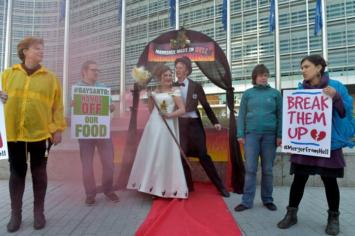 """Activists from Friends of the Earth Europe stage a """"marriage made in hell"""" protest against the Monsanto-Bayer merger outside the European Commission in Paris."""