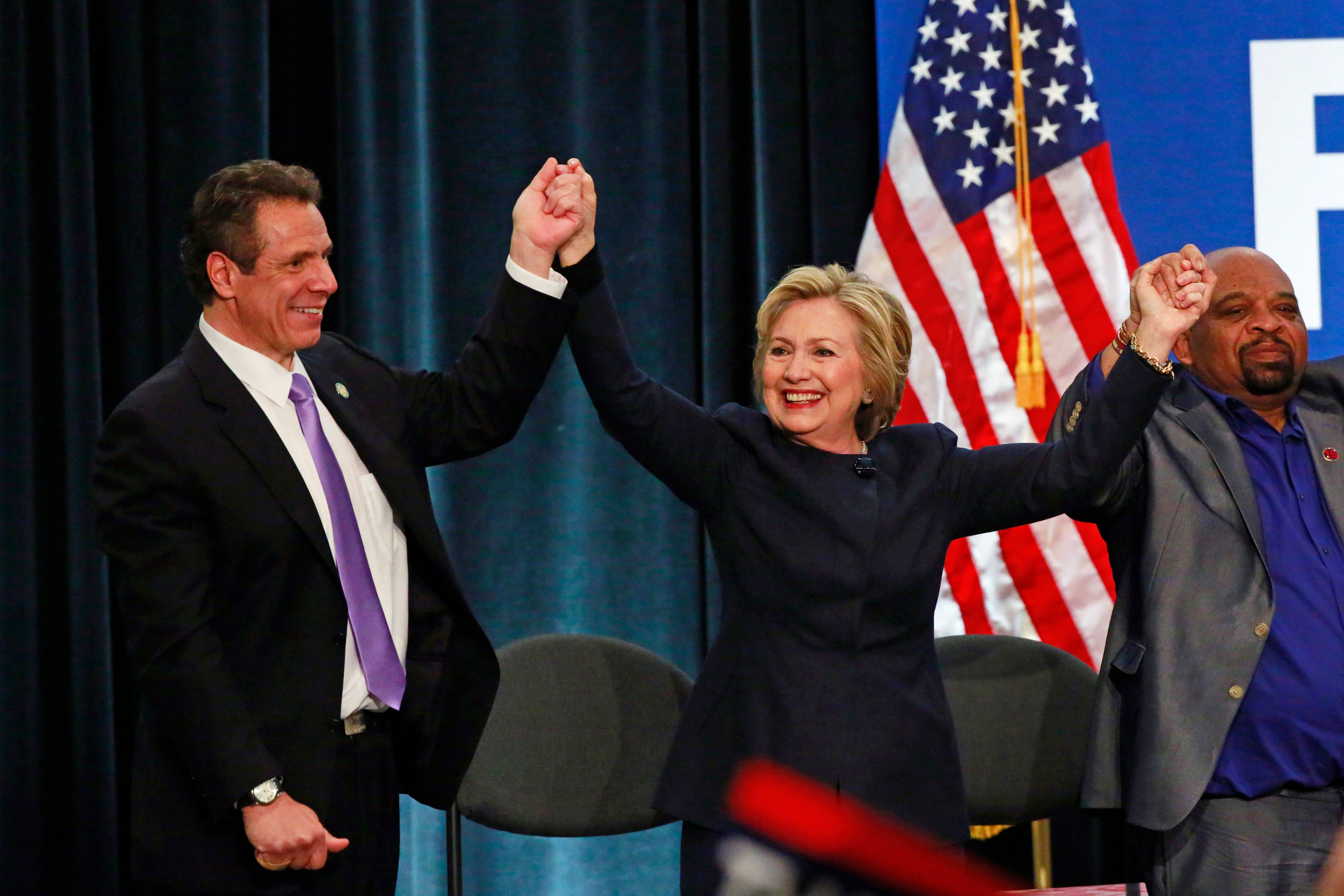 U.S. Democratic presidential candidate Hillary Clinton and New York Governor Andrew Cuomo (L) stand on stage after addressing at a rally to celebrate the state of New York passing into law a $15 minimum wage in New York April 4, 2016.  REUTERS/Lucas Jackson