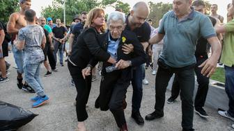 The mayor of Greeces second city, Thessaloniki, Yiannis Boutaris (C), 75-years-old, is helped after being assaulted by suspected far-right members at a rally in Thessaloniki on May 19, 2018. - The mayor of Greece's second city Thessaloniki was hospitalised early on May 20, 2018 after an assault by suspected far-right members at a rally, officials said. Yiannis Boutaris had to be escorted from an event commemorating the massacre of Black Sea Greeks in Turkey during and after World War I when members of the crowd turned violent. (Photo by - / Eurokinissi / AFP) / The erroneous mention[s] appearing in the metadata of this photo by - has been modified in AFP systems in the following manner: [May 19, 2018] instead of [May 20, 2018]. Please immediately remove the erroneous mention[s] from all your online services and delete it (them) from your servers. If you have been authorized by AFP to distribute it (them) to third parties, please ensure that the same actions are carried out by them. Failure to promptly comply with these instructions will entail liability on your part for any continued or post notification usage. Therefore we thank you very much for all your attention and prompt action. We are sorry for the inconvenience this notification may cause and remain at your disposal for any further information you may require.        (Photo credit should read -/AFP/Getty Images)