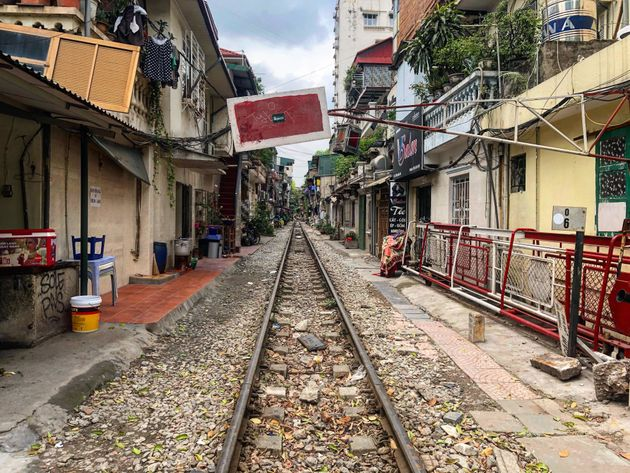 In the crowded streets of smoggy Hanoi, a train passes very, very close by people's