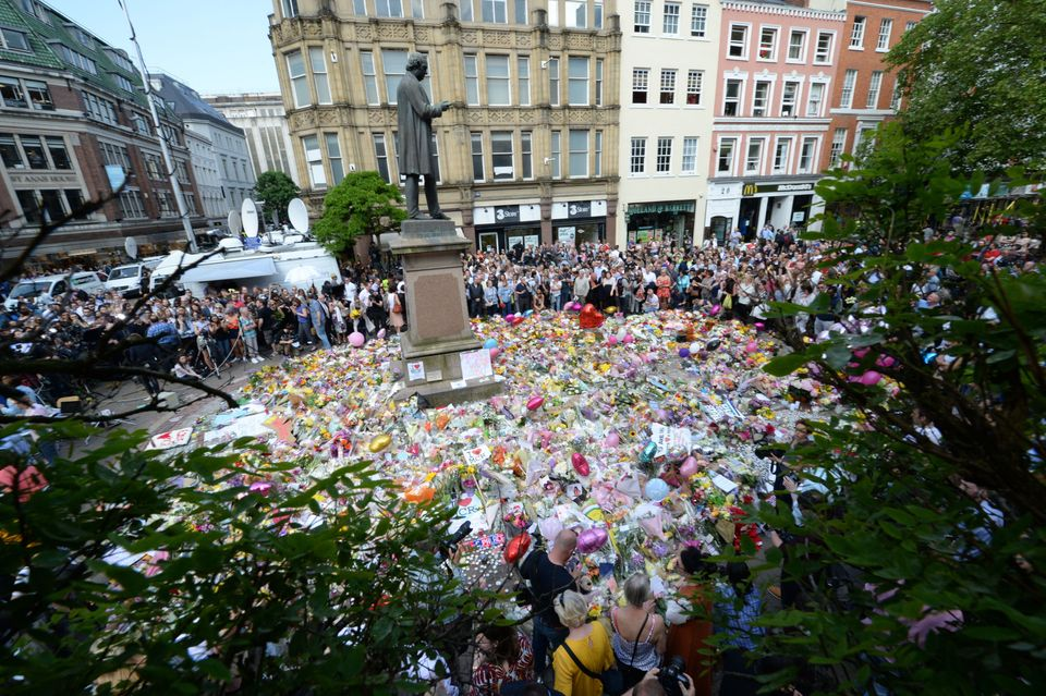 Crowds look at the floral tributes after a minute's silence in St Ann's Square,