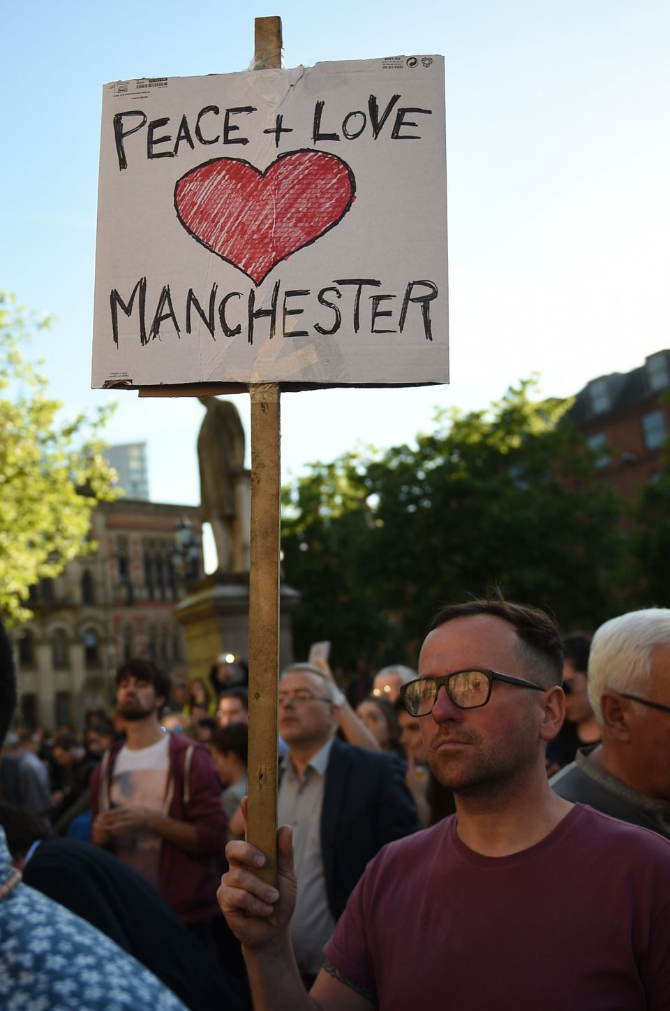 A man holds a banner reading 'Peace and Love Manchester' during a vigil in Albert Square in Manchester...