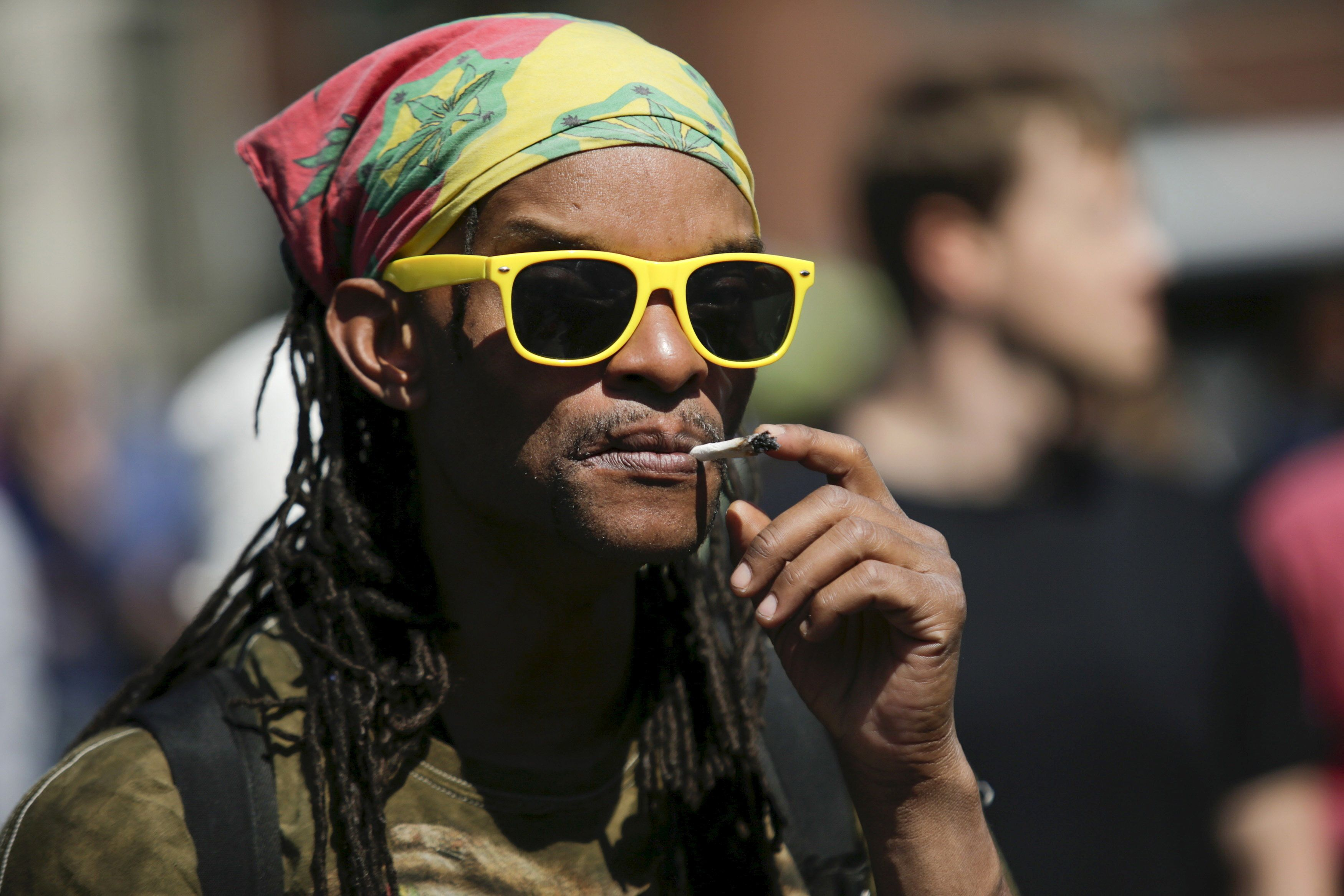 A man smokes a joint while people take part in a rally calling for marijuana to be legalized at Union Square in New York May 2, 2015. REUTERS/Eduardo Munoz