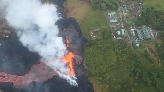 PAHOA, HI - MAY 21:  Lava erupts and flows from a Kilauea volcano fissure, near to the Puna Geothermal Venture (PGV) plant (TOP R), on Hawaii's Big Island on May 21, 2018 near Pahoa, Hawaii. Officials are concerned that 'laze', a dangerous product produced when hot lava hits cool ocean water, will affect residents. Laze, a word combination of lava and haze, contains hydrochloric acid steam along with volcanic glass particles.  (Photo by Mario Tama/Getty Images)