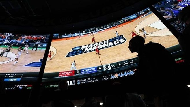 People wait in line to bet on the NCAA college basketball tournament at the Westgate Superbook sports book in Las Vegas. The