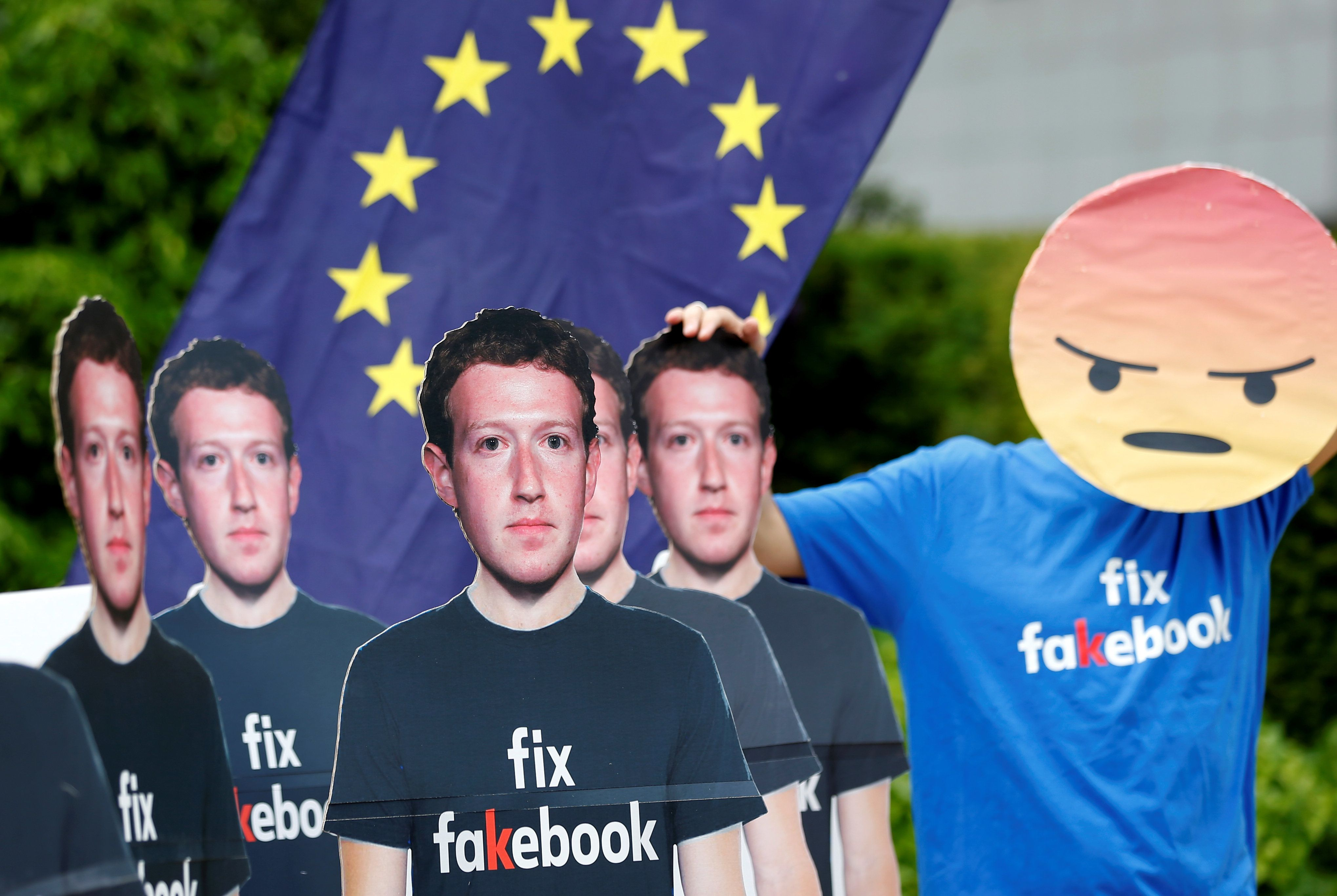 A protester holds an European Union flag next to cardboard cutouts depicting Facebook CEO Mark Zuckerberg during a demonstration ahead of a meeting between Zuckerberg and leaders of the European Parliament in Brussels, Belgium May 22, 2018. REUTERS/Francois Lenoir