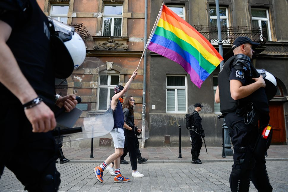 A man carries a rainbow flag next to police at the Pride Parade.