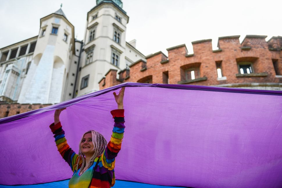 A woman holds a huge rainbow flag during the Pride Parade in Krakow.