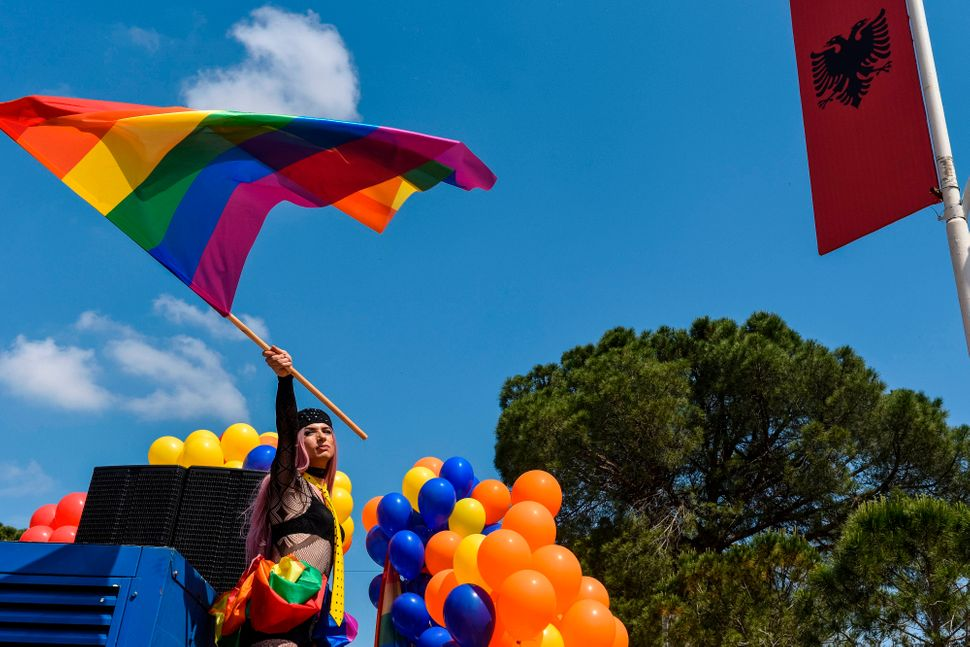 An Albanian LGBTQ activist waves a rainbow flag as she attends Tirana Gay Pride to mark the International Day Against Homopho