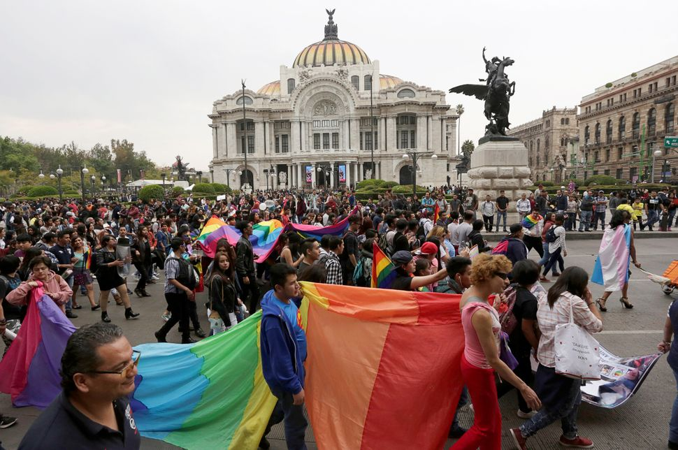 Members of the LGBTQ community carry the rainbow flag during the Lesbian and Gay Pride rally at the Bellas Artes Palace in Me