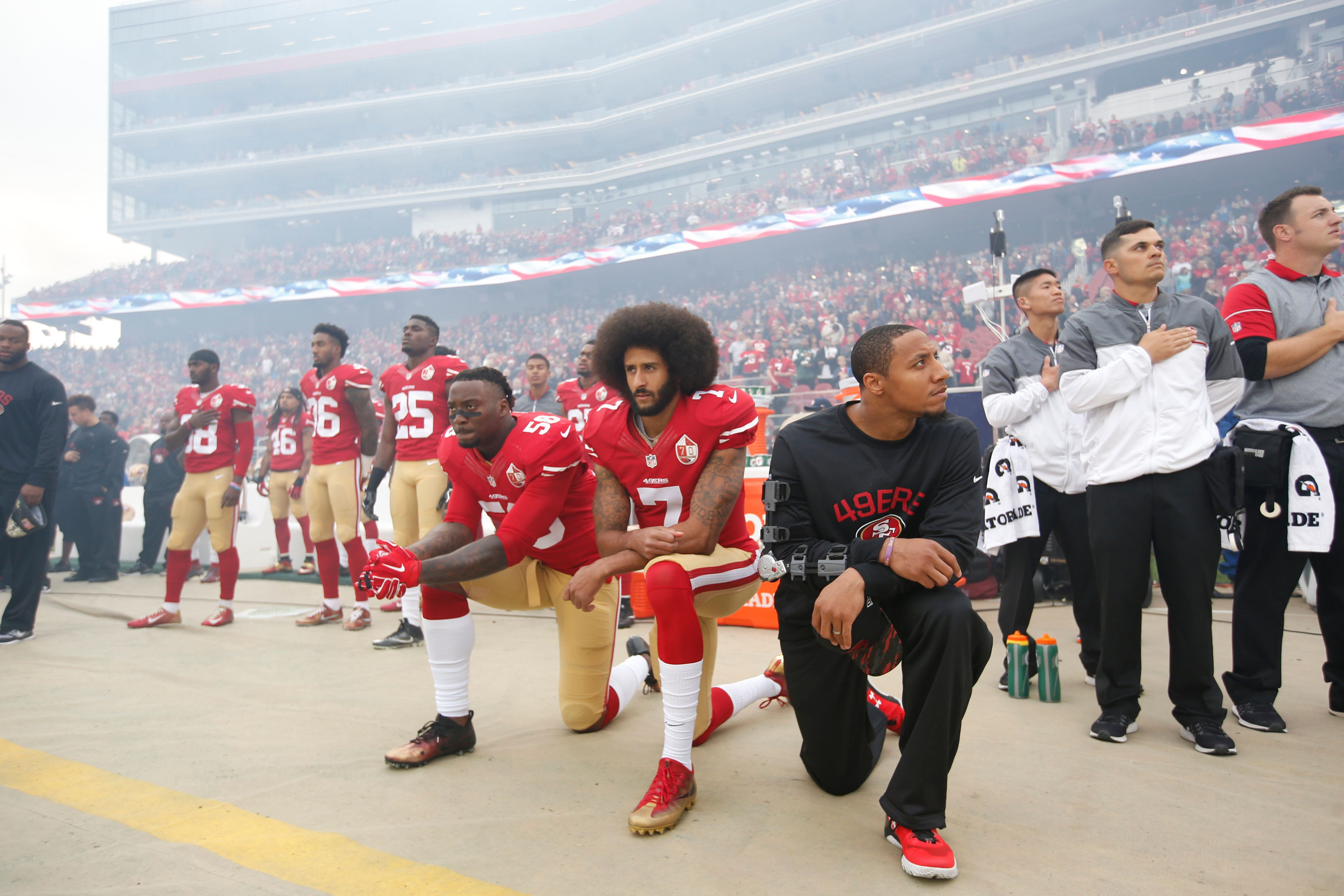 Colin Kaepernick, center, protesting with fellow players Eli Harold (left) and Eric Reid (right) in December