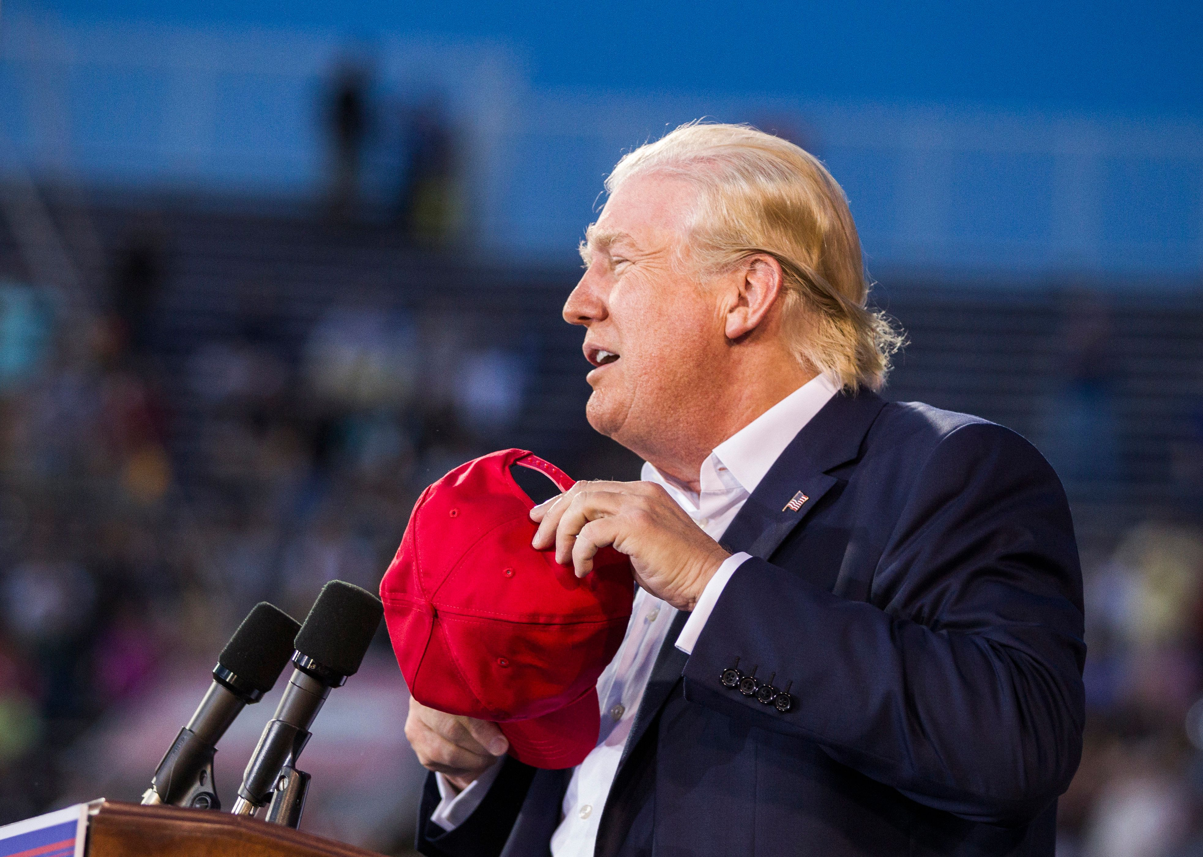 MOBILE, AL- AUGUST 21: U.S. Republican presidential candidate Donald Trump removes his hat to show that his hair is real during a political rally at Ladd-Peebles Stadium on August 21, 2015 in Mobile, Alabama. The Donald Trump campaign moved tonight's rally to a larger stadium to accommodate demand. (Photo by Mark Wallheiser/Getty Images)