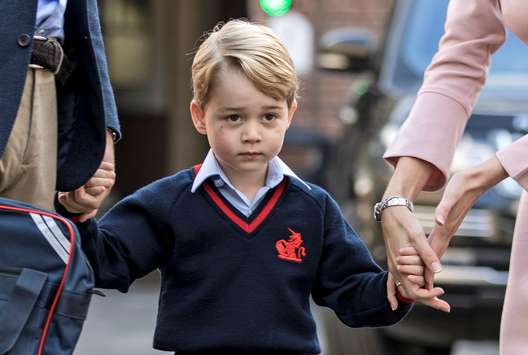 Helen Haslem, head of the lower school and Britain's Prince William hold Prince George's hands as he...