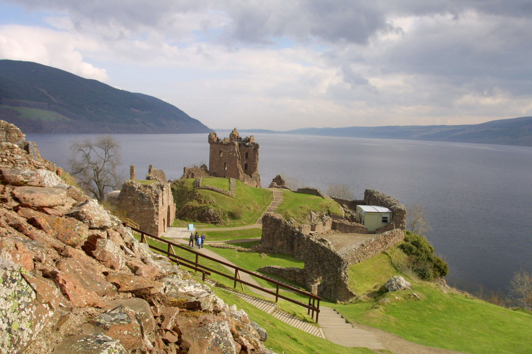 The ruined Urquhart Castle towering over the western shore of Loch Ness at Drumnadrochit. The loch is famed for the myt