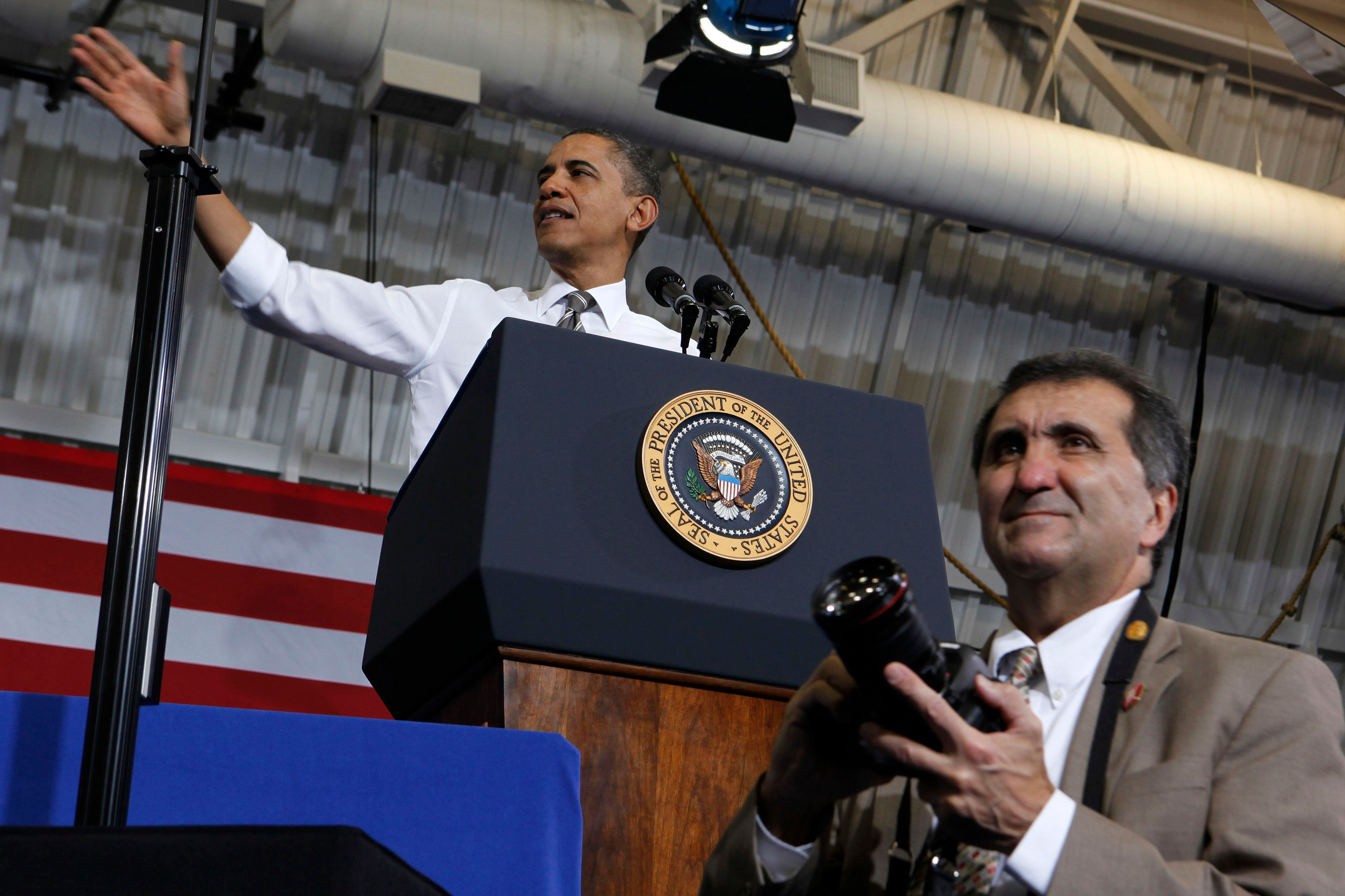 U.S. President Barack Obama talks about American energy while his official photographer Pete Souza stands in front the podium at Prince George's Community College in Largo, Maryland, March 15, 2012.      REUTERS/Larry Downing       (UNITED STATES - Tags: POLITICS)